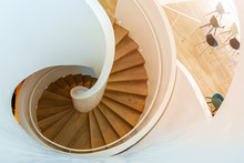Top View Beautiful Spiral Staircase Consist Of Wooden Tread And Riser, White Bold Railing, Balustrade And Round Handrail, Interior Of Furniture Showroom With. Iconic Spiral Stairway.