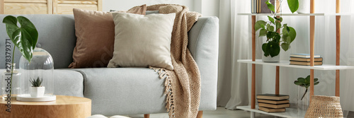 Fotografiet Close-up of gray comfortable sofa in modern apartment - panorama