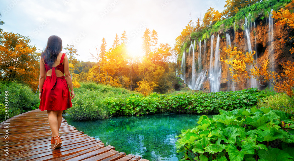Fototapety, obrazy: Woman traveler walking on wooden path trail with lakes and waterfall landscape in Plitvice Lakes National Park, UNESCO natural world heritage and famous travel destination of Croatia.