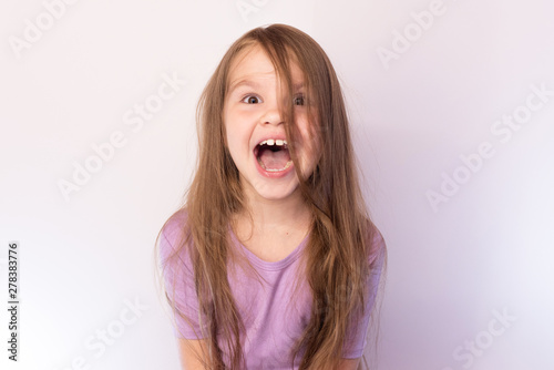 Fotografia, Obraz  Little girl with her hair, his mouth wide open, screaming, on a light background