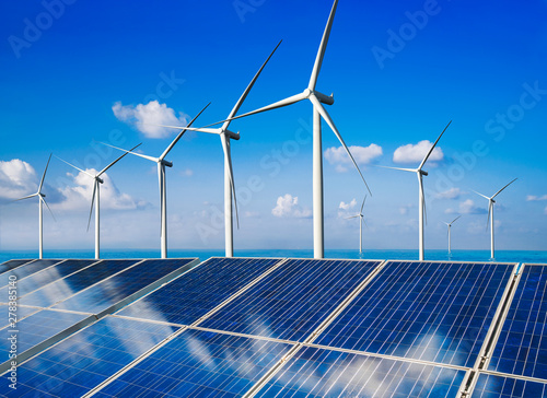 Obraz Solar energy panel photovoltaic cell and wind turbine farm power generator in nature landscape for production of renewable green energy is friendly industry. Clean sustainable development concept. - fototapety do salonu