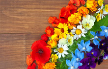 A Rainbow Of Colorful Flowers: Red Poppies, Orange Marigolds, Yellow Daisies, Green Clover Leaves, Blue Delphinium And Purple Pansies On A Wooden Background. Copy Space, Flat Lay. Summer Background