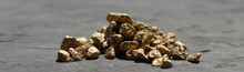 Golden Sones. A Pile Of Gold Nugget Grains, On Gray Cement Background, Copy Space