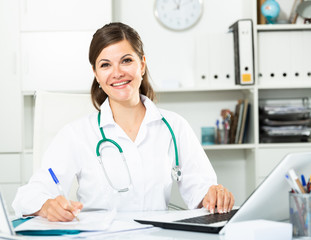 Smiling woman doctor working effectively in her office