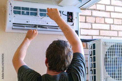 Fényképezés  Male technician repairing air conditioner outdoors