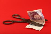 Scissors Cut British Pound Over Red Background