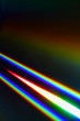 canvas print picture Beams of light refracting and creating a rainbow spectrum of colours against a black background
