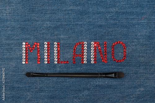 Fotografie, Obraz Inscription Milano, inlaid rhinestones on denim. Top view.
