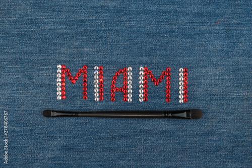 Fotografering Inscription Miami, inlaid rhinestones on denim. Top view.