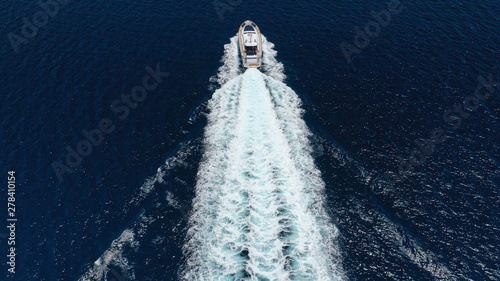 Obraz na plátně  Aerial drone tracking photo of luxury yacht with wooden deck cruising in deep bl