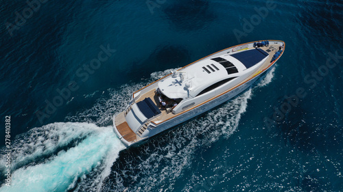 Aerial drone tracking photo of luxury yacht with wooden deck cruising in deep blue waters of Mykonos island, Cyclades, Greece