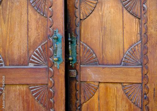 Photo Half open door ajar, warm wooden door decorative with bronze handle bars