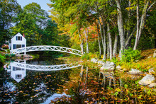White Footbridge Reflecting On The Water Among The Colorful Autumn Foliage