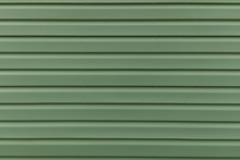 The Texture Of The Green Board Of The Exterior Of The House Siding Panel. Parallel Abstract Stripes Line