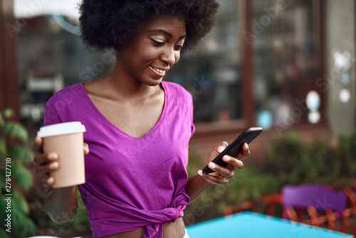 Cheerful afro-american girl typing on mobile phone outdoors - 278427710