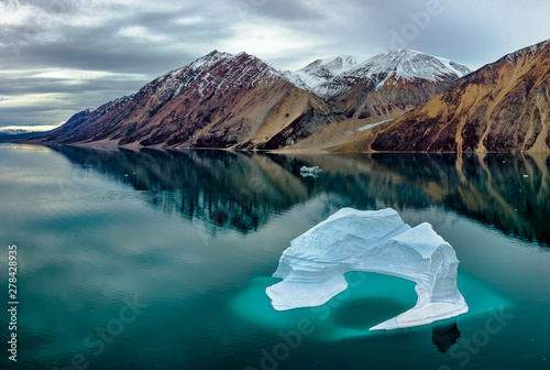 Fotografie, Obraz Iceberg in the shape of circle with a hole in the center in Greenland