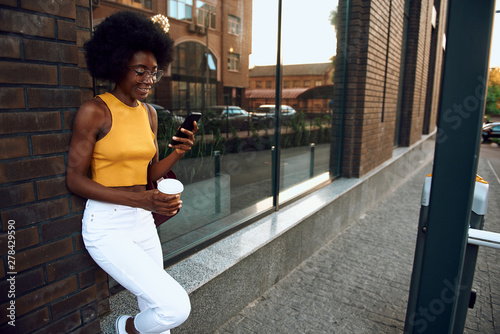 Happy young woman is using smartphone outdoors - 278429590