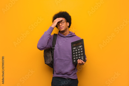Photo Young african american student man holding a calculator worried and overwhelmed