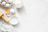 Baking Cooking Ingredients Flour Eggs Rolling Pin Butter And Kitchen Textile On Bright Grey Concrete Background. Top View Copy Space. Cookies Pie Or Cake Recipe Mockup