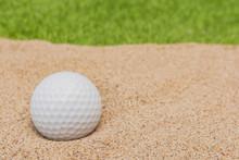 White Golf Ball In Sand Bunker On Golf Court.