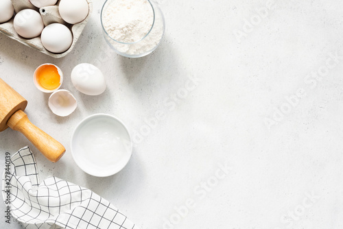 Fototapeta Baking Cooking Ingredients Flour Eggs Rolling Pin Butter And Kitchen Textile On Bright Grey Concrete Background. Top View Copy Space. Cookies Pie Or Cake Recipe Mockup obraz