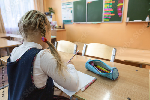 Photo Female pupil is on academic detention in school class for completion of student