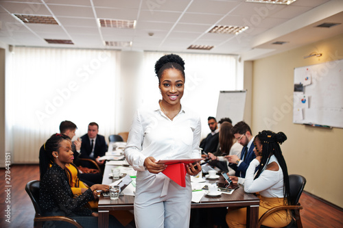 Fototapety, obrazy: Face of handsome african american business woman, holding tablet on the background of business peoples multiracial team meeting, sitting in office table.