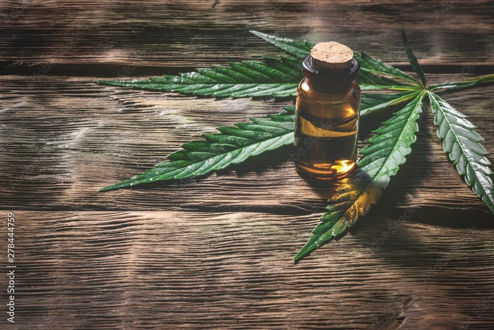 Fototapeta Cannabis essential oil in the vial with a green leaf on a wooden table background with a copy space. Herbal medicine concept.
