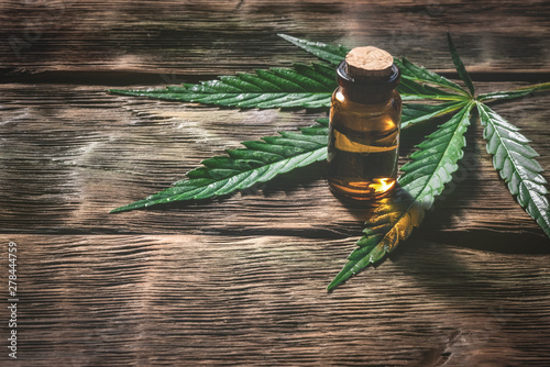 Photo Cannabis essential oil in the vial with a green leaf on a wooden table background with a copy space