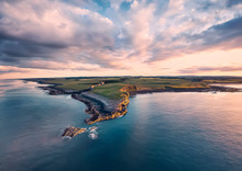 View From The Air To  The Embleton Sea Shore, North Sea, The Cliff With Seagulls, Ruins And Green Fields. Sunset With Dramatic Clouds. England Countryside. UK.  Aerial Footage, Drone Flight