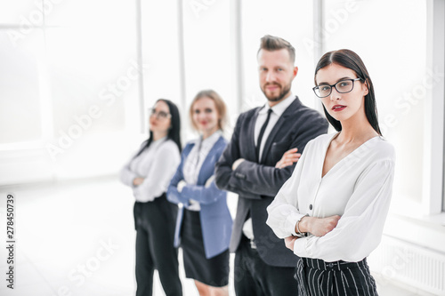 successful business woman standing in front of her business team