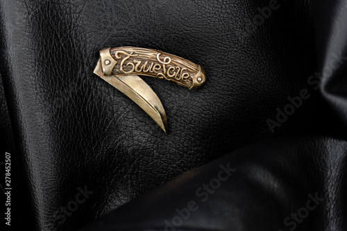 Brass brooch on leather coat Fototapet