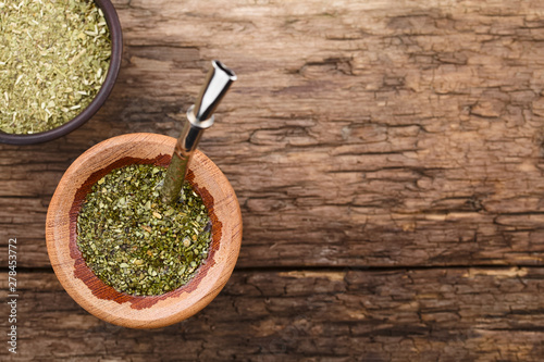 Traditional South American Yerba Mate tea in wooden mate cup with bombilla metal straw serving as a sieve, photographed overhead with copy space (Selective Focus on the top of the tea in the cup)