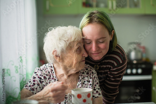 Canvastavla Portrait of elderly woman with her granddaughter at the table in the kitchen at home
