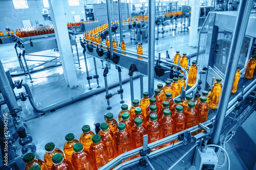 Conveyor belt, juice in bottles on beverage plant or factory interior in blue co Fototapete
