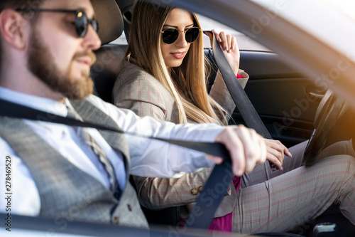 Fotografie, Obraz  Man and woman sitting in car putting on seat belt