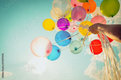 Fotografia Hand holding multi colored balloons done with a retro vintage instagram filter effect