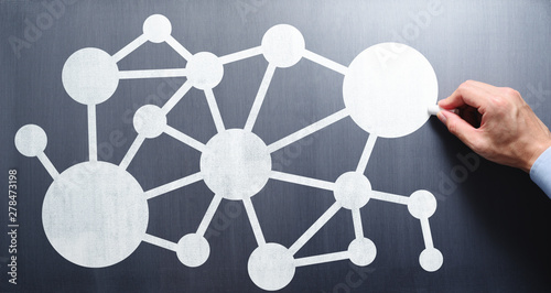 Network communication concept. Businessman drawing network structure on chalkboard.
