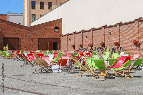 Fototapeta KRAKOW,POLAND - AUGUST 16, 2018: Street cafe corner with deck chairs in front of old brick wall. Kazimierz district obraz