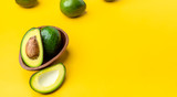 organic avocados half cut with seed and whole fruit in wood bowl on yellow table background.Healthy super foods for diet.Fresh vegetable from farm.keto food ingredients.banner for display content.