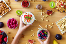 Top View On Wooden Table With Summer Breakfast, Female Hands Are Holding Glass Bowls With Organic Yoghurts. Low Calorie Diet Meal With Berries, Goji, Nuts, Granola, Chia, Fruits. Healthy Food Concept.