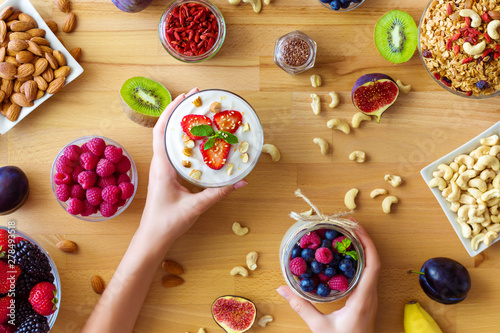 Fotografie, Obraz  Top view on wooden table with summer breakfast, female hands are holding glass bowls with organic yoghurts
