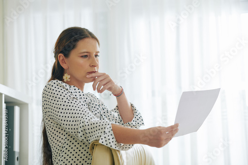 Poster de jardin Route Portrait of pensive female entrepreneur reading document with good offer from investor
