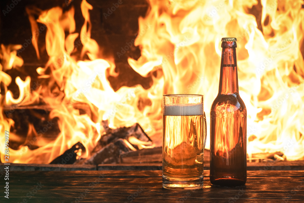 Fototapety, obrazy: Beer in a mug and a bottle of alcohol on a wooden table on a burning fire in a fireplace background.