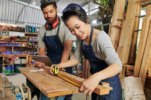Poster de jardin Route Positive female carpenter in denim apron measuring wooden plank with tape measure
