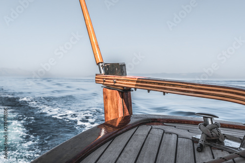 Foto  Wooden rudder on small wooden boat and blue sea