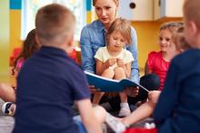 Teacher And Children Reading A Book In The Preschool