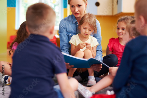 Poster de jardin Route Teacher and children reading a book in the preschool