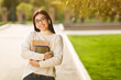 canvas print picture - Happy girl with books listening music in campus