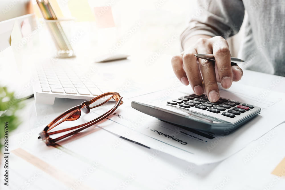 Fototapety, obrazy: Close up of businessman or accountant hand holding pencil working on calculator to calculate financial data report, accountancy document and laptop computer at office, business concept